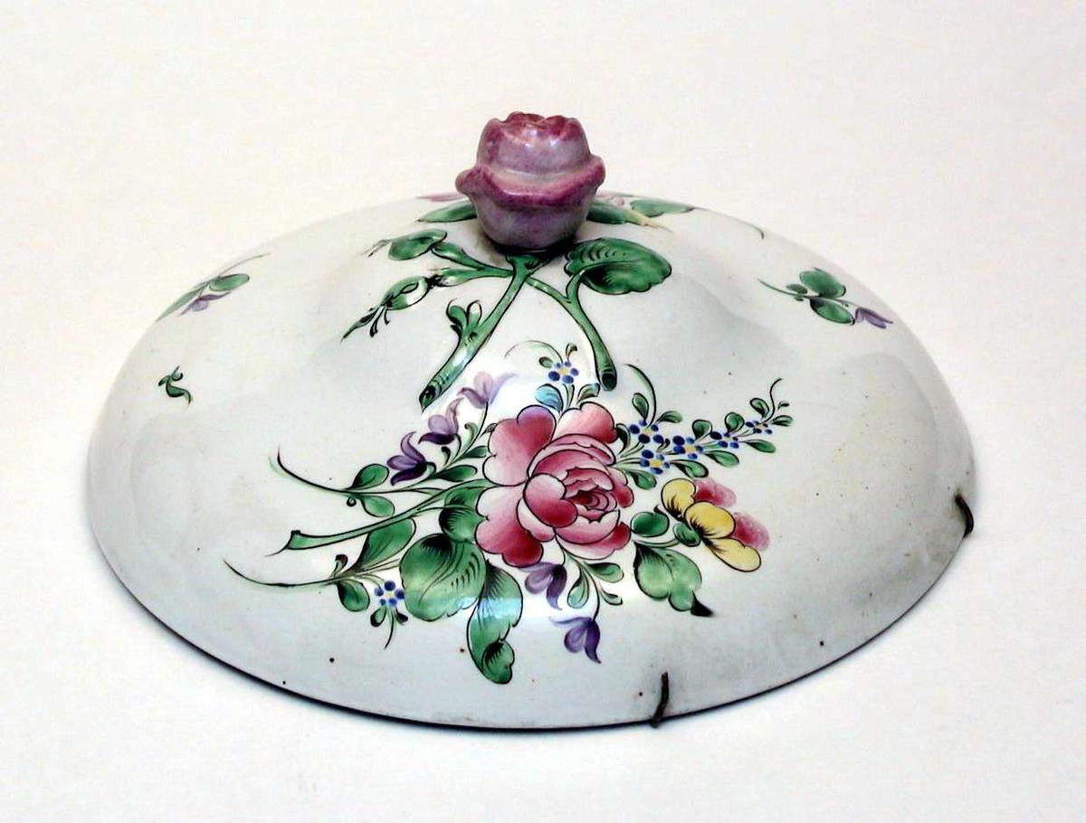 Rundt lokk i kremfarget keramikk med polykrom blomsterdekor. Lokkgrepet er en rose. Fatet eller terrinen som lokket har hørt til, mangler.