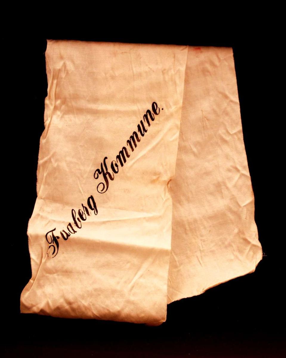 Bånd i kremfarget silke. På båndet står: Faaberg Kommune