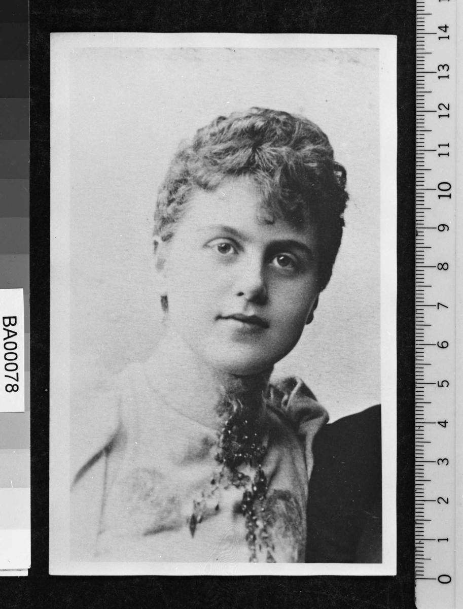 Portrettfotografi av ung dame med oppsatt frisyre og høyhalset kjole med puffermer og brosje ved halslinningen.