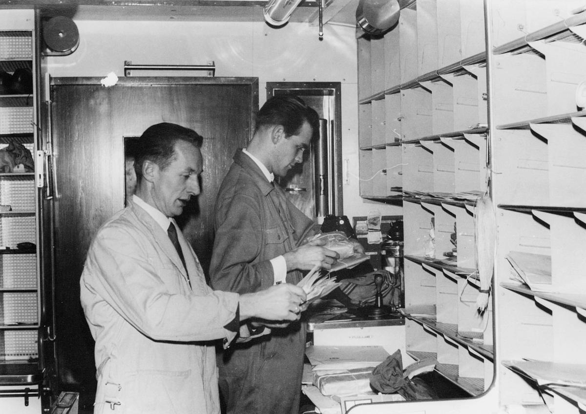 postbehandling, sortering, sorteringsreoler, 2 menn