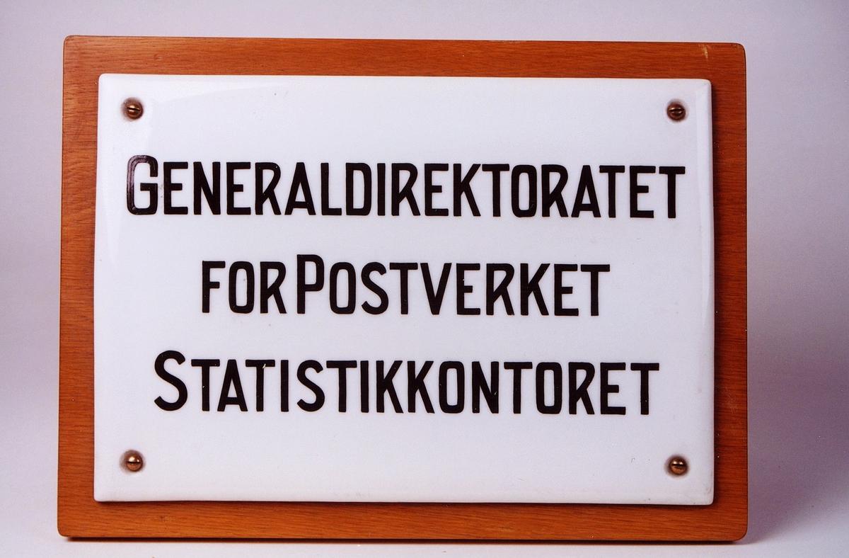 Skiltet er påsatt treplate. Sort skrift. Det er brukt i Poststyret. Generaldirektoratet for postverket, statistikkontoret.