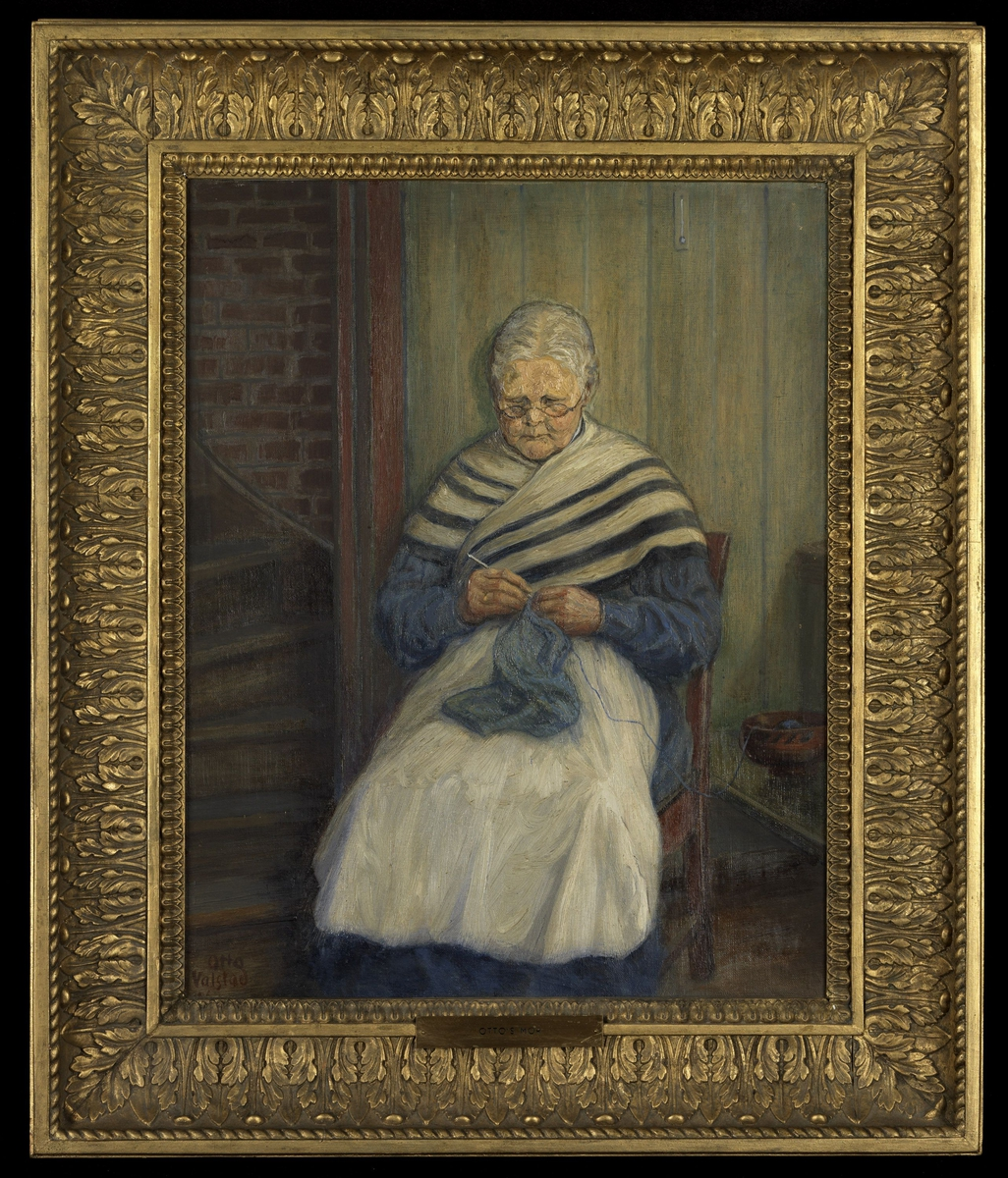 Kvinne gråhåret, sittende på stol, noe venstrev., strikkende, blå kjole, hvitt forkle, blått og hvitt sjal, trapp tilv.
