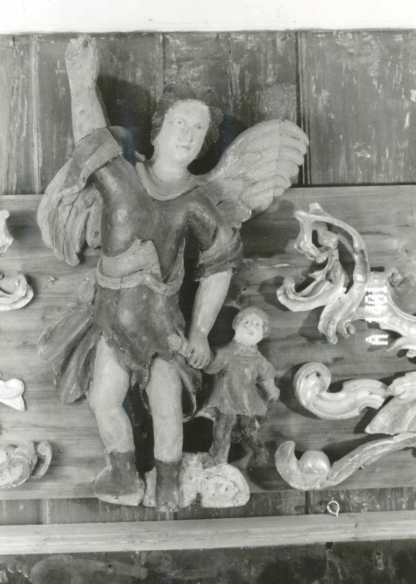 Engel m. utspilte vinger; v.arm løftet, leier barn v.h. hånd, gråblå kort drakt m. rødt; barnet i brunt