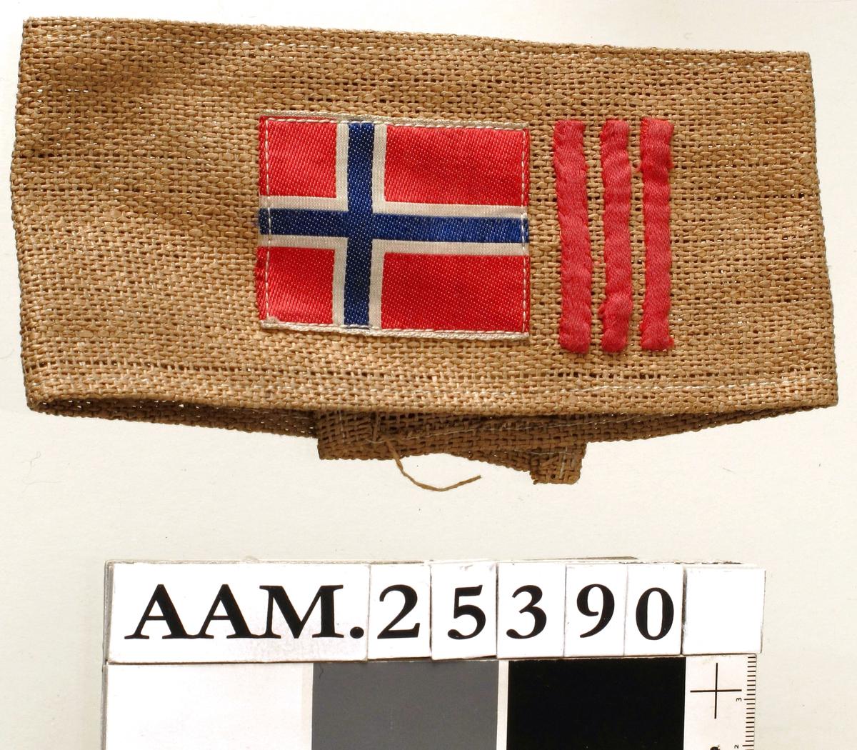 Armbånd m. påsydd norsk flagg og tre røde striper.