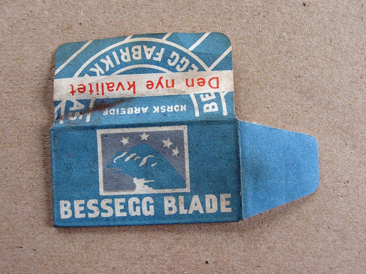 Pakke med ett barberblad fra Bessegg Fabrikker: Ytteremballasje av papir, inneremballasje av lett gjennomsiktig papir, barberblad.