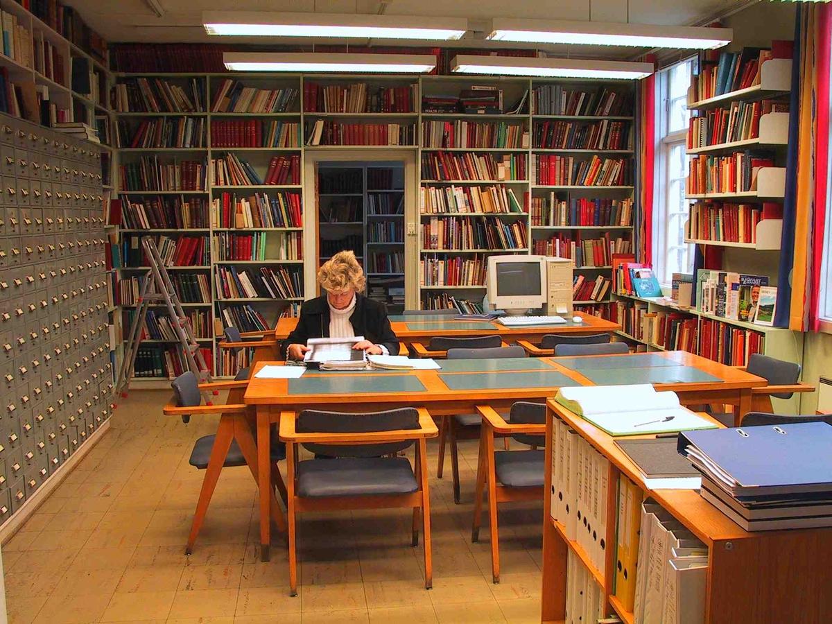 Arkivet. Lesesalen, sett mot øst. En lesesalsgjest, sitter med ansiktet vendt mot fotografen. Bord, stoler, veggene dekket av kartotekreoler og bokhyller.