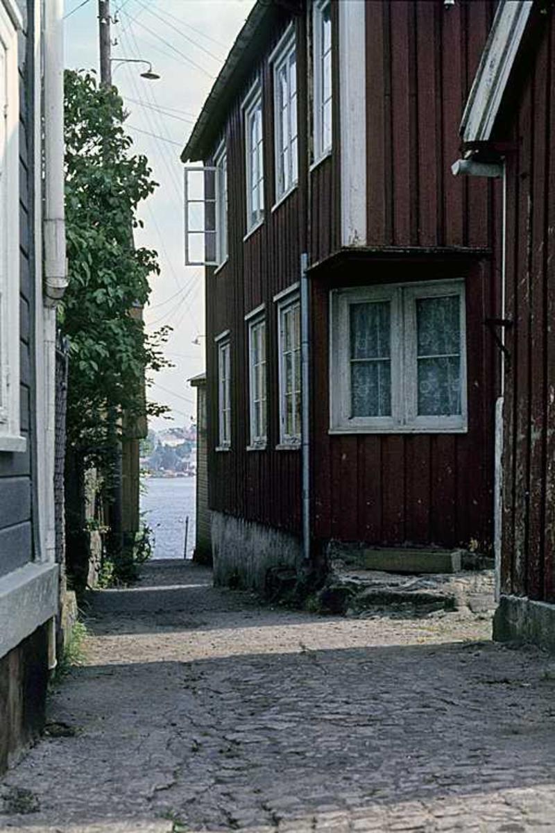 Gateparti, smalt smau i Kampebakken på Tyholmen, gløtt mot Byfjorden.