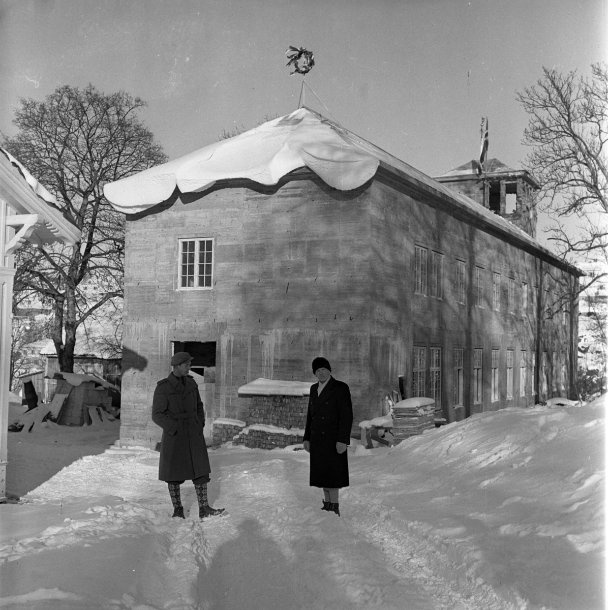 Aust-Agder-Museets første byggetrinn  - senere arkivfløy  Kranselag. Vinter med snøl. I forgrunnen Albert Ugland og Allan Johnsen. Mennene er kledd i vinterfrakk. Knestrømper og beksømstøvler.