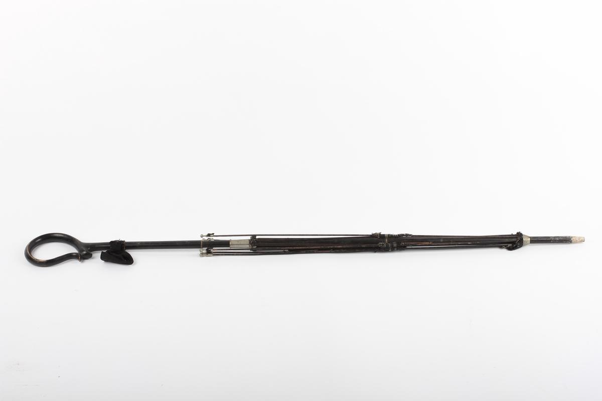 Form: Håndtaket formet som en løkke. Svart ripssløyfe i øvre ende av stangen. Rester av svart- og hvitstripet paraplystoff. Spiler - blikk? svartmalte og med blanke metallknotter ytterst. Merke på baksiden av en av spilene.