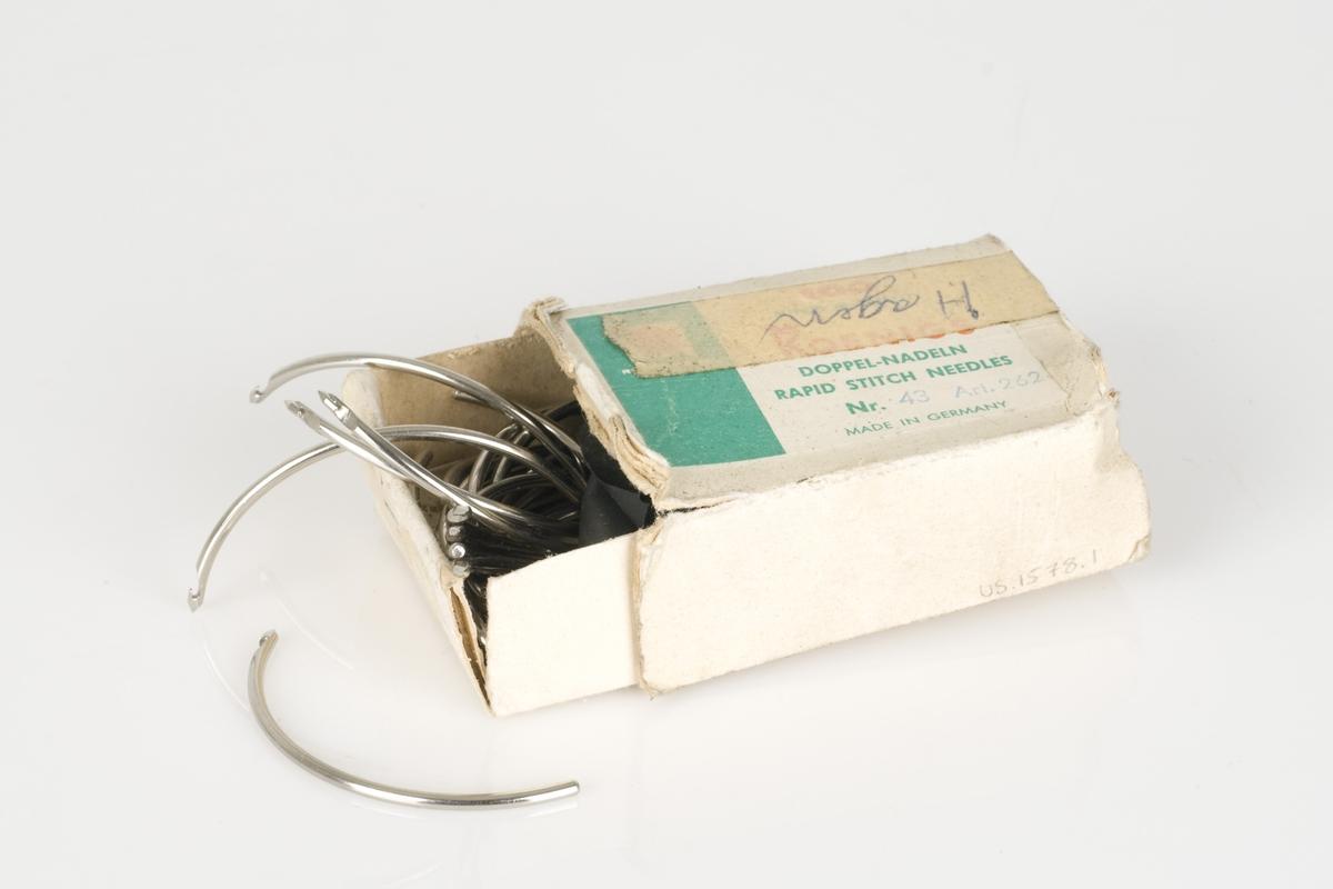 Durknåler av metall med innskrift.  Nålene ligger i en liten pappeske med påført tekst.