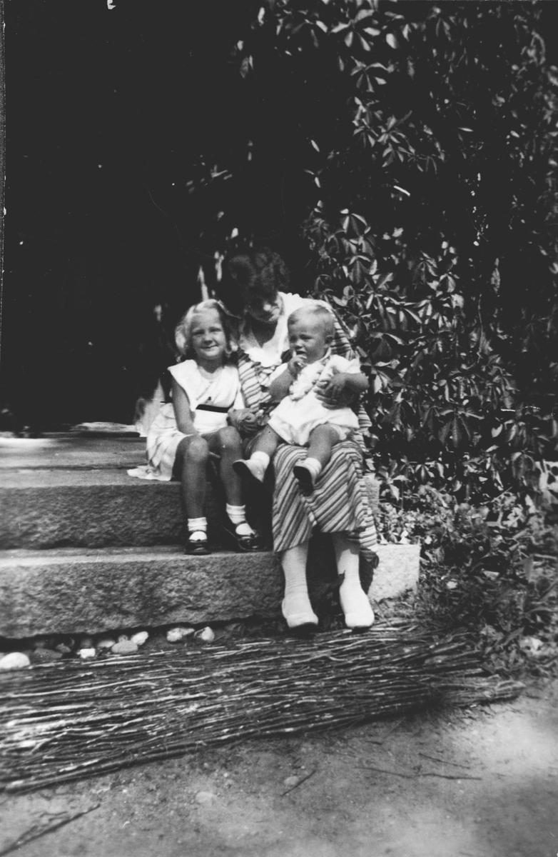 Kvinne m/to små barn sittende på trapp