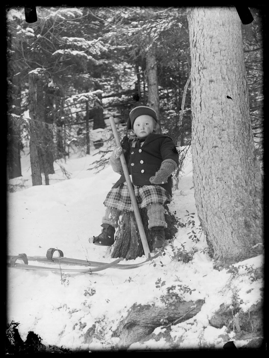 En liten jente som tar en hvil i vinterskogen.