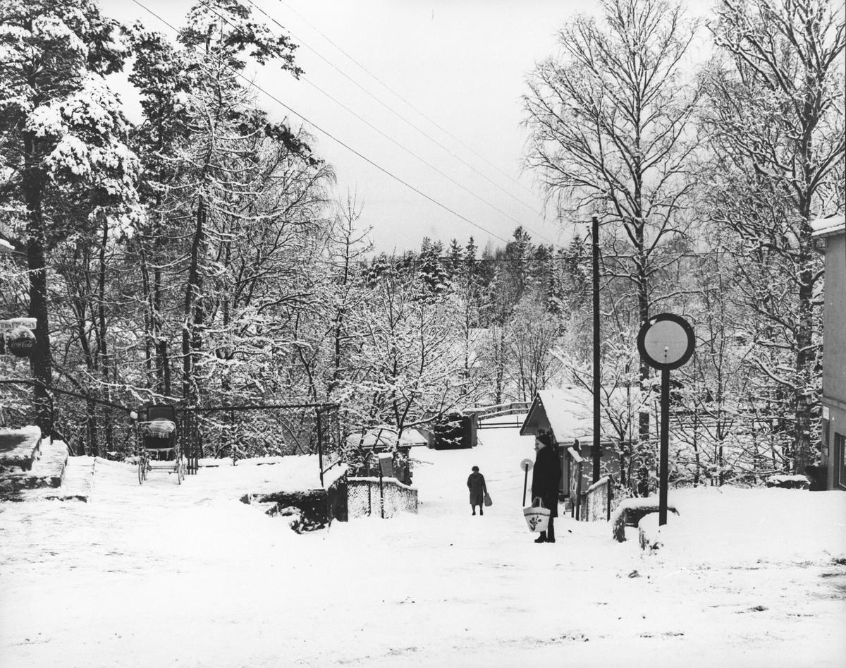 Oppegård sentrum, gangvei ned mot jernbanestasjon, utedo, kiosk. Vinter.