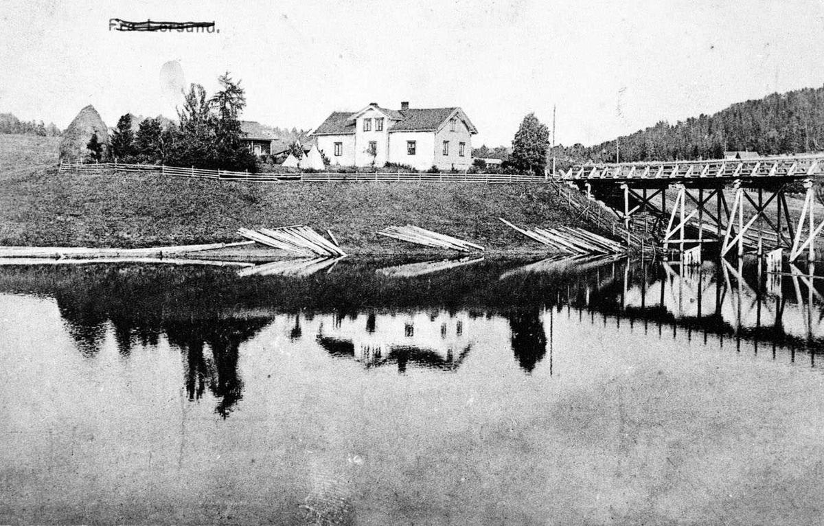 """Kjellerholen bru sett fra sørvest ca. 1910 Postkort merket """"Fra Leirsund"""" Brua er nå revet og erstattet med en ny. På bredden ligger fløtingstømmer"""