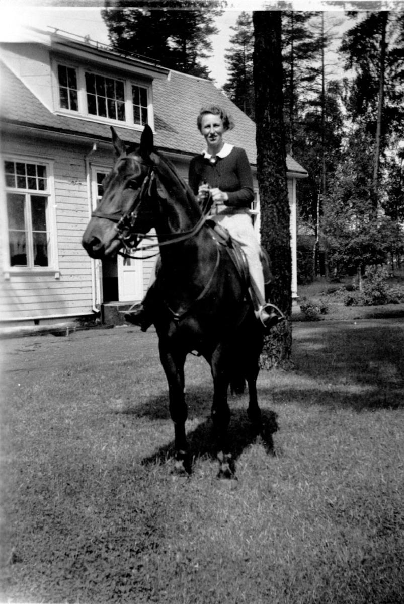 Kona til sanitetslege. Thordis D. på hest utenf. pensjon. Gard.