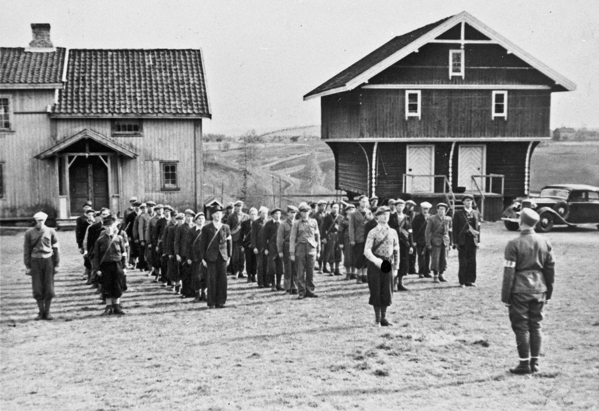 Hoel gård på Holt, Østsiden mot Minnesund. 5 tropper oppstilt. Tropp 6, Minnesund Øst. Karer fra Langseth og Habberstad. Harald Opstad (områdesjef), foran med ryggen til. Odd Bjerknes (troppsjef) foran troppen. Helt til venstre Ole Fredrik Hoel, eier av gården og nest - troppsjef.