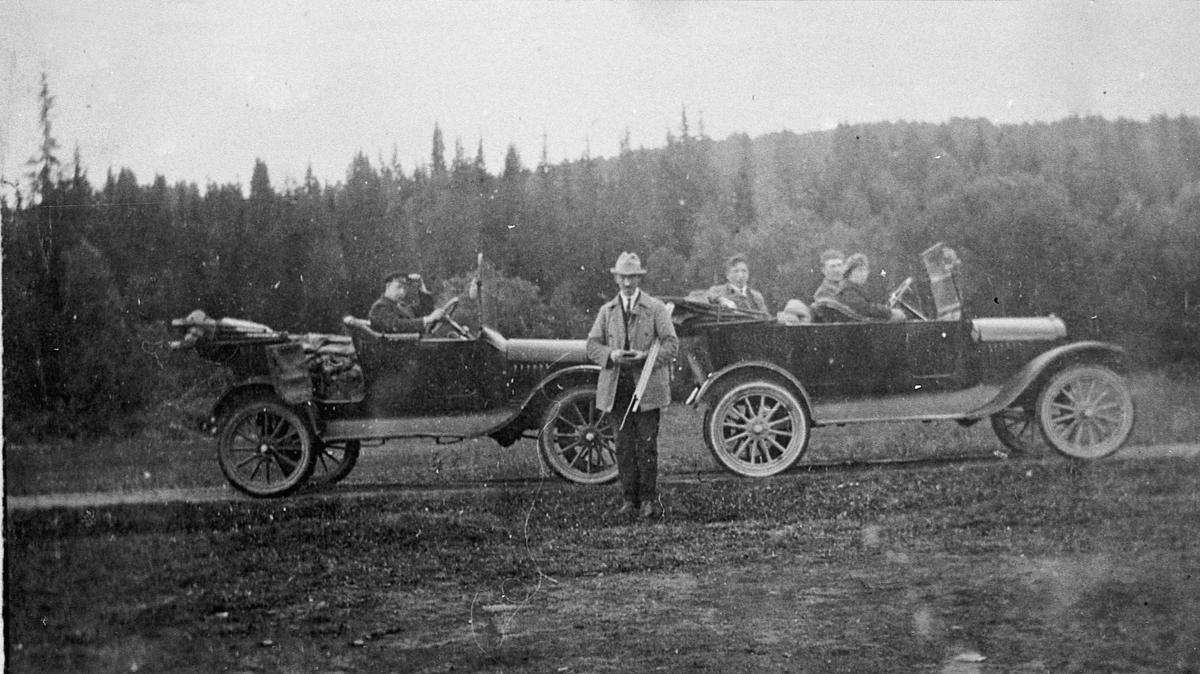 2 biler av mellomkrigsmodell. Skrukklia 1926. I bilen til venstre: Peder Lesja ved rattet. Amund Millidal står foran. I bilen til høyre: Jacob og Hjørdis Millidal i forsetet. Nicolai Tronsbråten bak. Bilen til høyre ble brukt som drosje.