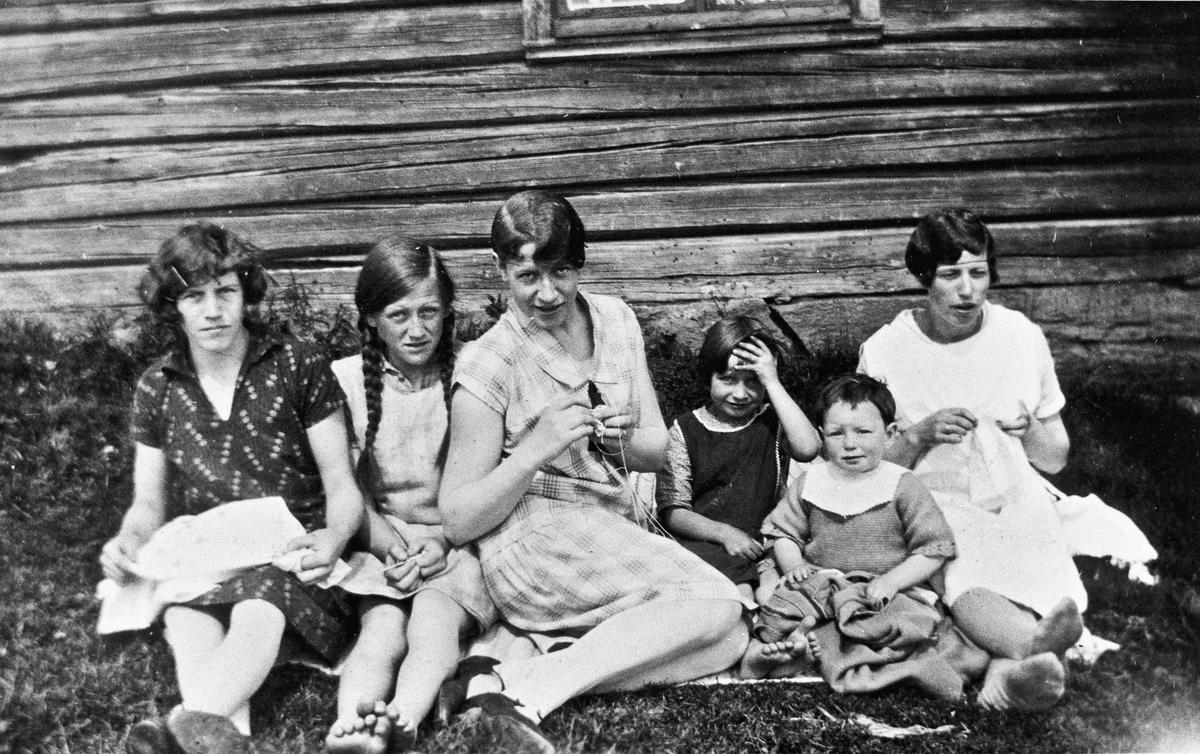 Kvinner og barn utenfor tømmerhus.