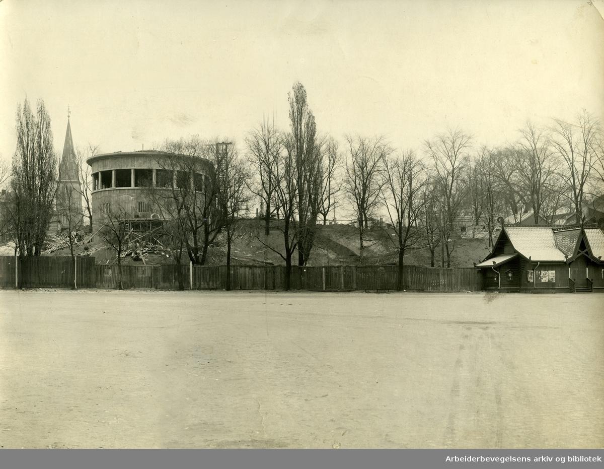"""Restaurant """"Skansen"""" med Johannes kirke i Rådhusgaten i bakgrunnen til venstre, som ble revet i 1928. Foran til høyre står den gamle ventehallen til båtene som traffikerte i Oslofjorden,.ca. 1926"""