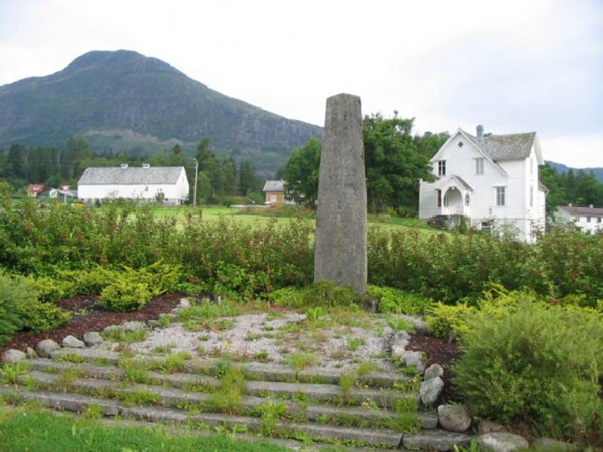 Ca 4 m høg hoggen stein, festet i en betongsokkel med trappearrangement i stein opp til den. Ca 1m bred nede og ca 60 cm bred oppe