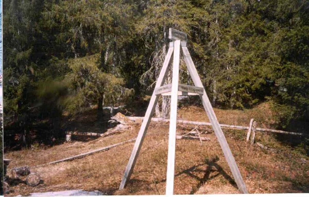 Et triangel av tre med treplater med tekst, en topplate og en navneplate på hver side av triangelet.