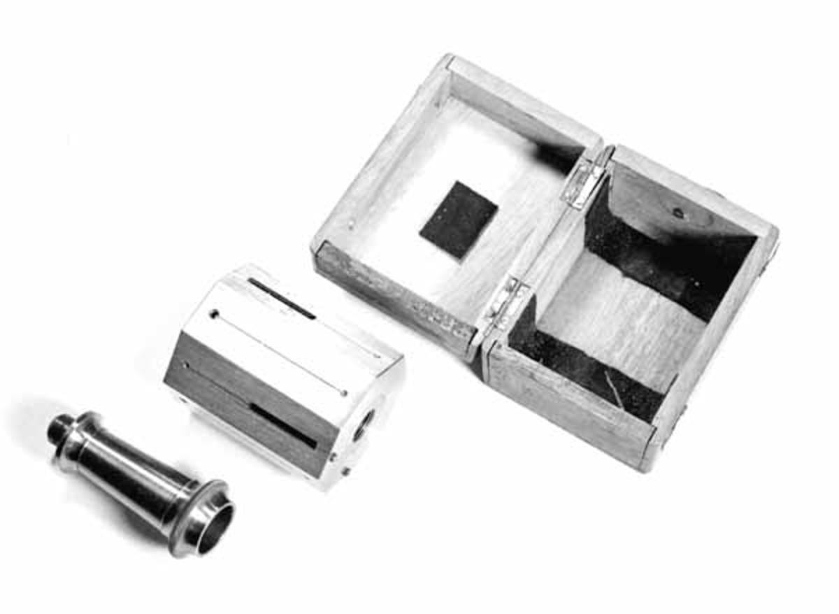 Vinkeltrommel i et lite treskrin av fremmed treslag. Vinkeltrommelen består av en åttekantet messingtrommel, i den ene enden er det en åpning. En sylinder går inn i trommelen. Rundt åpningen er det en kant. På trommelens sider er det smale spalter. EN tynn metalltråd langs annenhver spalte.