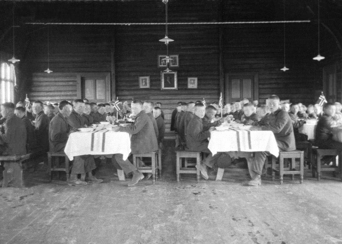 Interiør fra matsalen på Toftes Gave, Nedre Sund, Helgøya. Gutter ved dekkede bord pyntet med flagg.