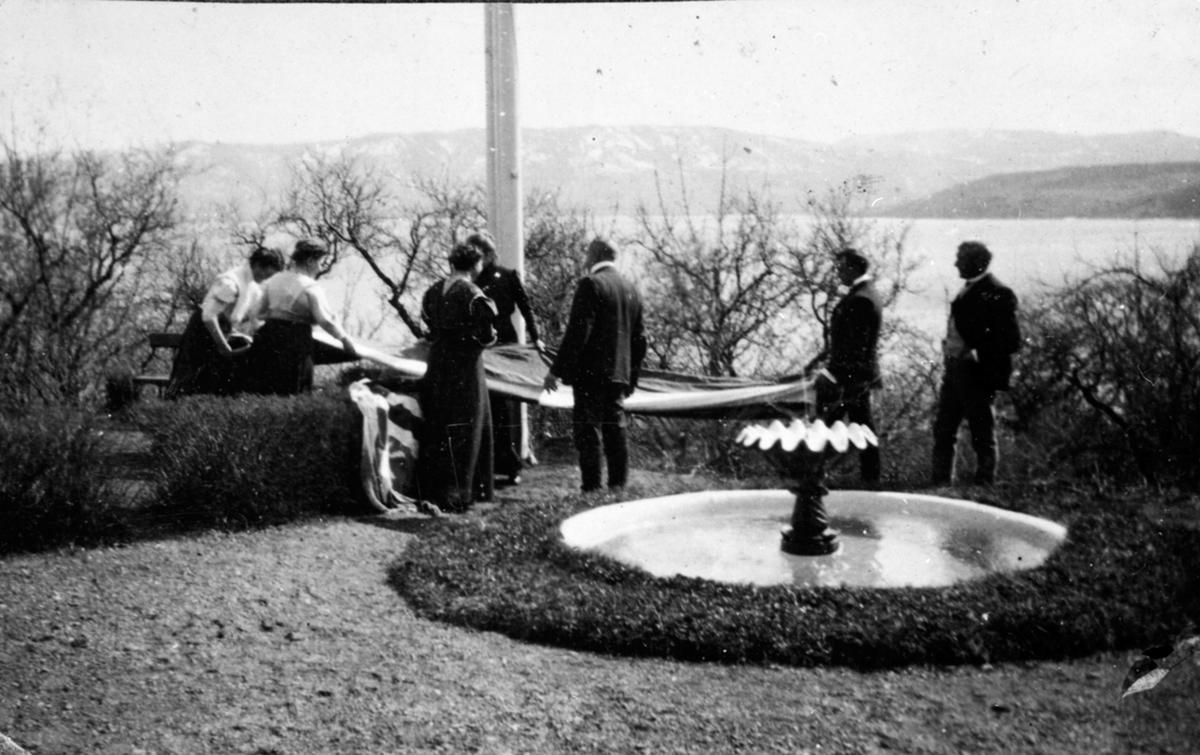 Flaggheisning på Hovelsrud, Helgøya. Gruppe personer ved fontenen og flaggstanga. Utsikt mot Mjøsa og Skreia.