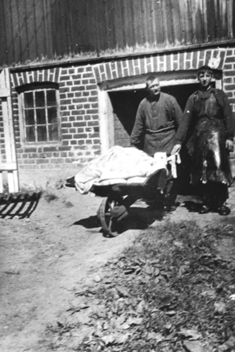 Bruvold mølle, Moelv. 2 ukjente menn med trillebår foran bryggerhuset.