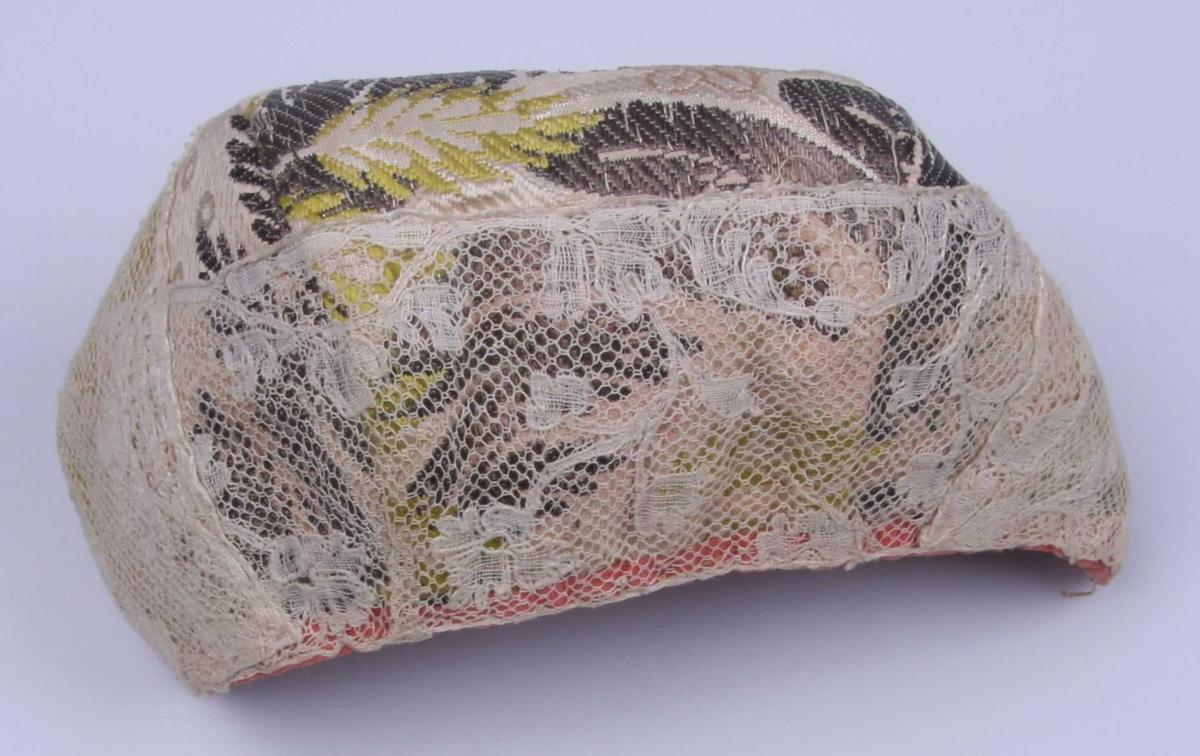 Av blekrød silke brochert med blomster og bladmønster i sølv, rosa (to sjatteringer), grønt, gulgrønt og litt blått. Hetten består av tre deler: Ett pannenakke-stykke og ett stykke på hver side. Kantet med laksrøde silkebånd og påsydd en 6 cm. bred Mechlin-knipling med barokk-blomstermønster. Fôret med rosa linstrie, med mellomfôret nestet til. Spor etter knytebånd.