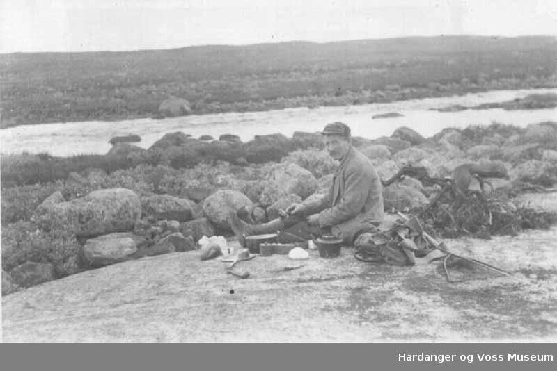 Mann, lue, sekk, fisk, kjeler, elv, på fjellet. Ola O. Hereid spiser sjølvfiska fisk. Bremafoten