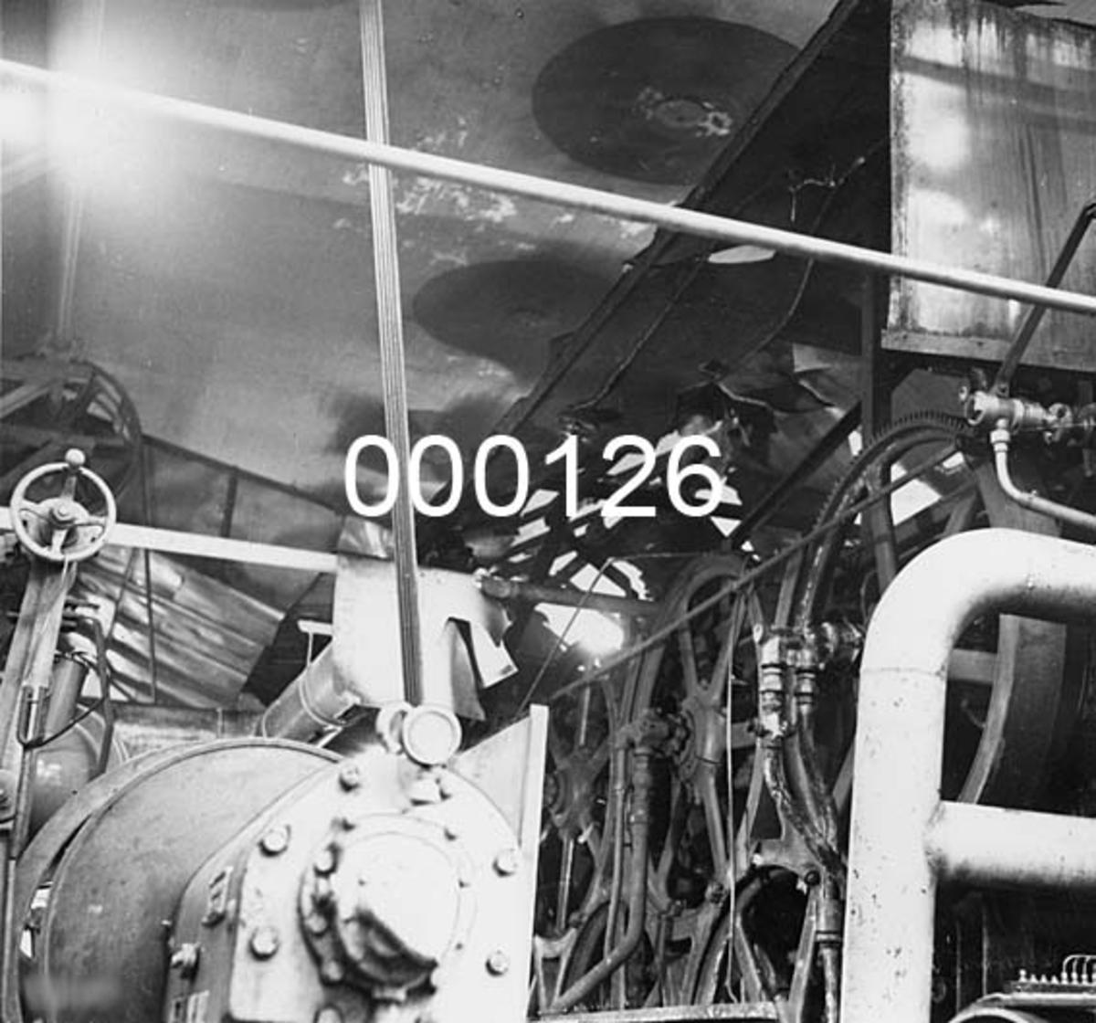 Interiørbilde fra Drammenselvens Papirfabrikker på Geithus på Modum i Buskerud.  Fotografiet viser en del av PM III slik det så ut etter en mindre brann i januar 1961.  Brannen oppsto i 2. sylinderparti.  Brannvesenet var raskt på pletten og skadene ble begrenset til et par filtrer og noe av hetta over maskinen.