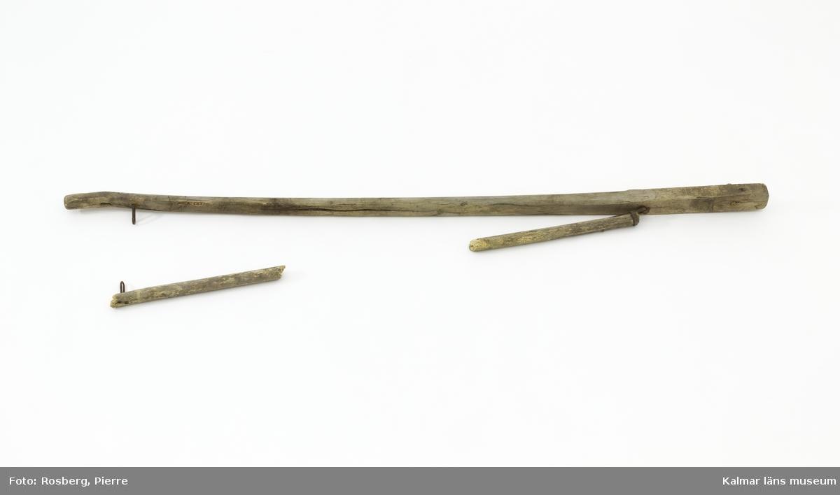 """KLM 11844. Parskaklar, dialektalt """"skakeldrag"""". Till vagn. Kombinerad parstång och skaklar av trä med järndetaljer. Två stycken skaklar fästa i varandra med järnringar. En av skaklarna är kraftigare och längre och har i ena änden ett borrat hål för fäste i vagn, i hålet en träplugg. Den mindre skakeln har gått av och delar saknas, en mindre lös bit finns sparad. För anspänning med två hästar. På den större skakeln skrivet: Bäckebo."""