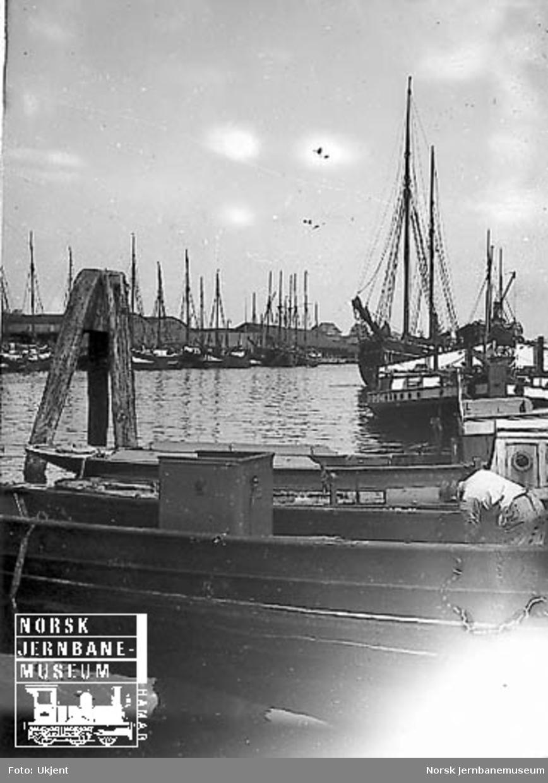 Ukjent havneanlegg med båter og fiskeskøyter