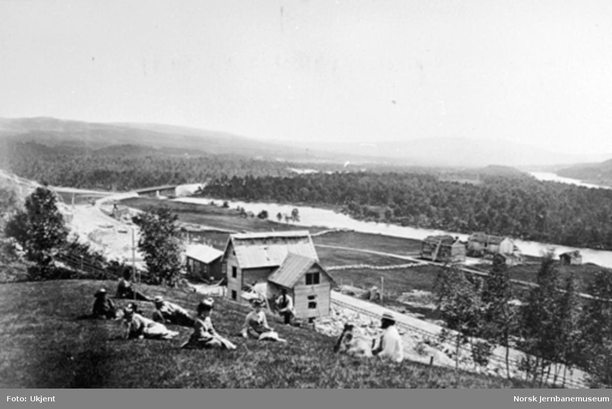 Glåmos (Jensvold) stasjonen under bygging; folk i forgrunnen og brua over Glomma i bakgrunnen