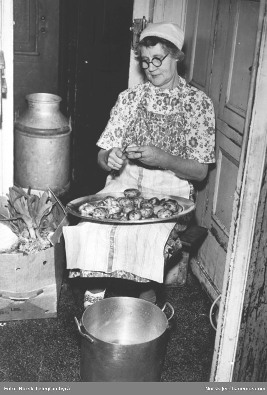 En kokke i gang med potetskrelling i spisevogn