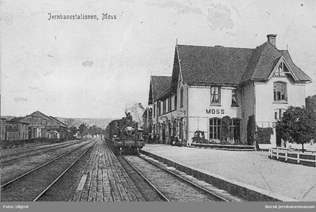 Moss stasjon med stasjonsbygningen og damplokomotiv med tog