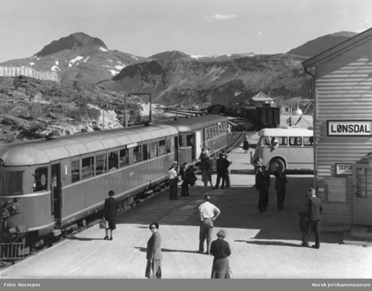 """Lønsdal stasjon med reisende til """"Nordlandsekspressen"""" fra ankommende buss; motorvogn type 6 nr. 18262 fremst."""