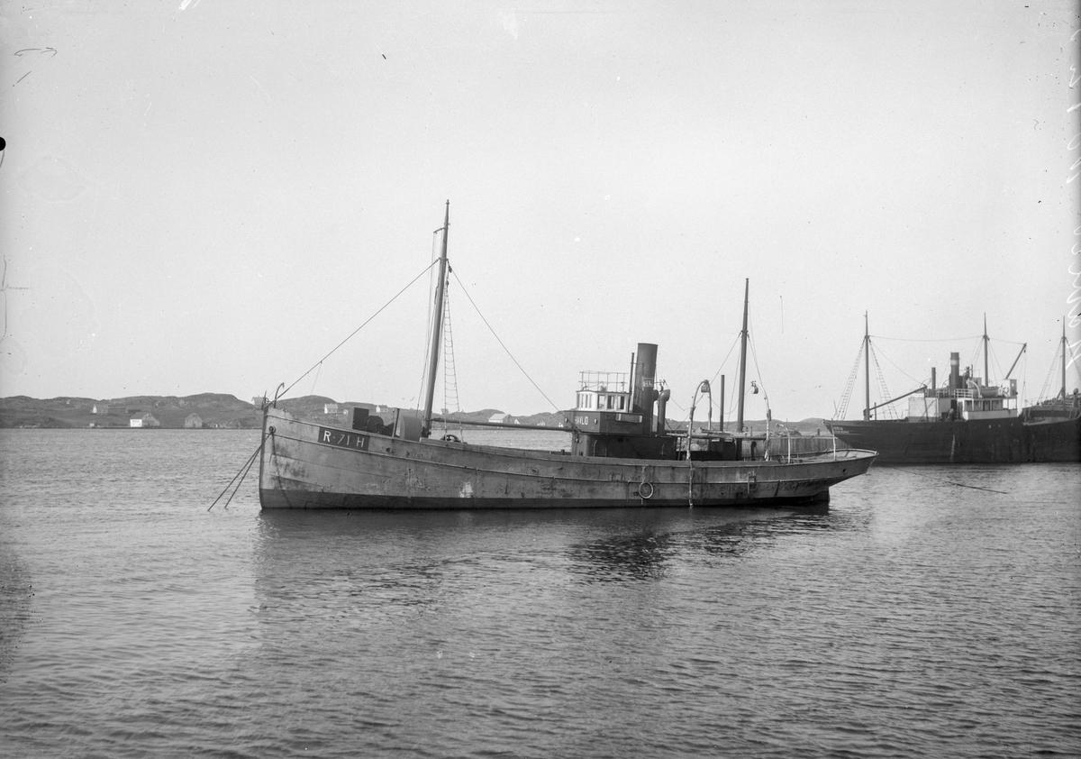 """Dampskipet/fiskeåbåten D/S """"Havlid"""" ankret opp i Karmsundet. Noe større skip like bak. I bakgrunnen land og noen hus."""