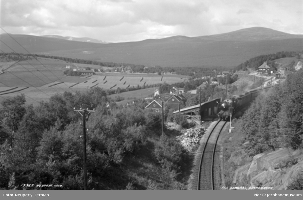 Innkjøring til Dombås stasjon sørfra, tog med damplokomotiv på vei ut fra stasjonen