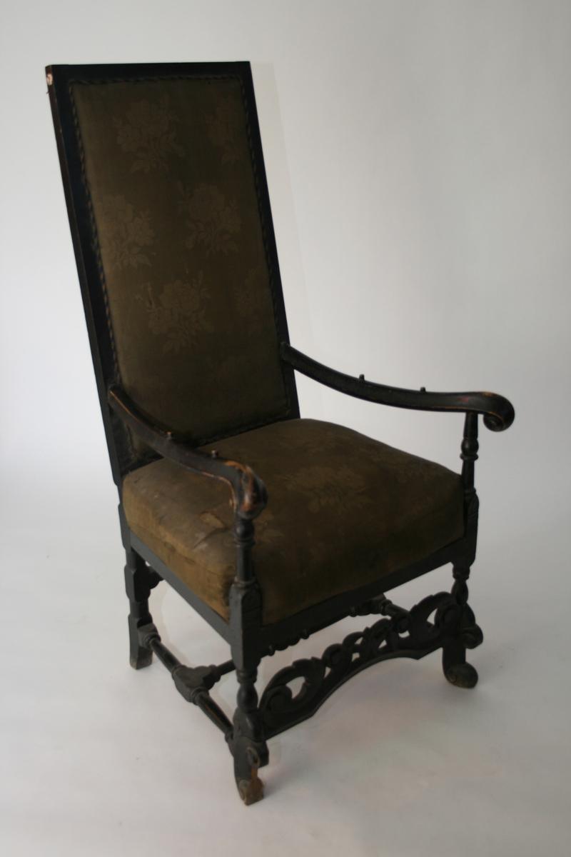 Høy, sort armstol, barokk. Gulblomstret ulltrekk. Dreide bein, utskjæringer.