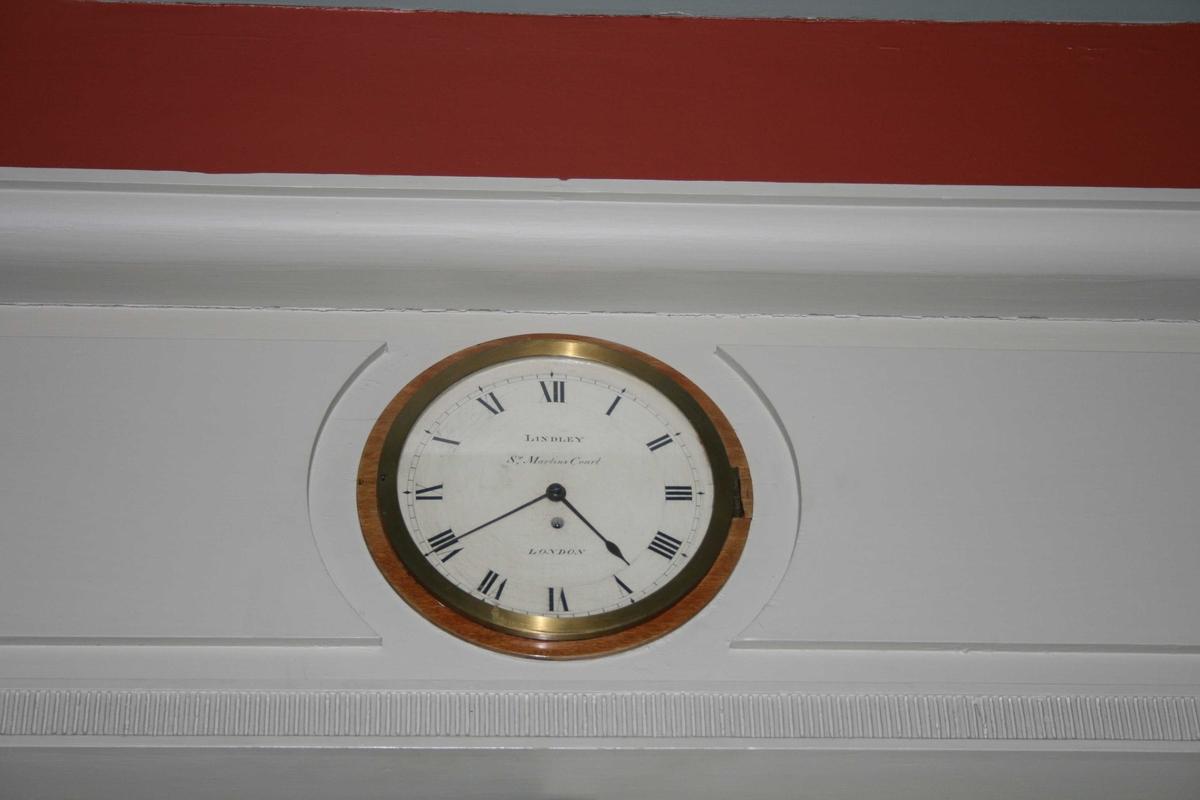 Urskive innfelt i veggen. Urverket er montert i ei kasse på baksida av urskiva, på andre siden av veggen. Skal være det opprinnelige uret som Casten Anker anskaffet i London i 1802.
