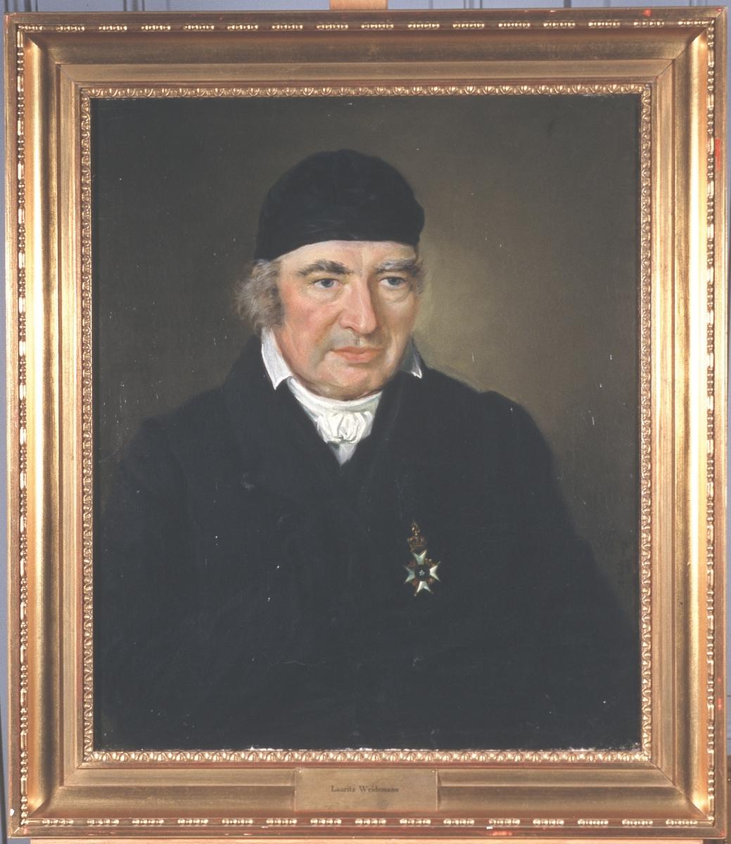 Portrett av Lauritz Weidemann. Mørk drakt, svart hodeplagg, kalott.. Orden (Nordstjerneordenen) på brystet.