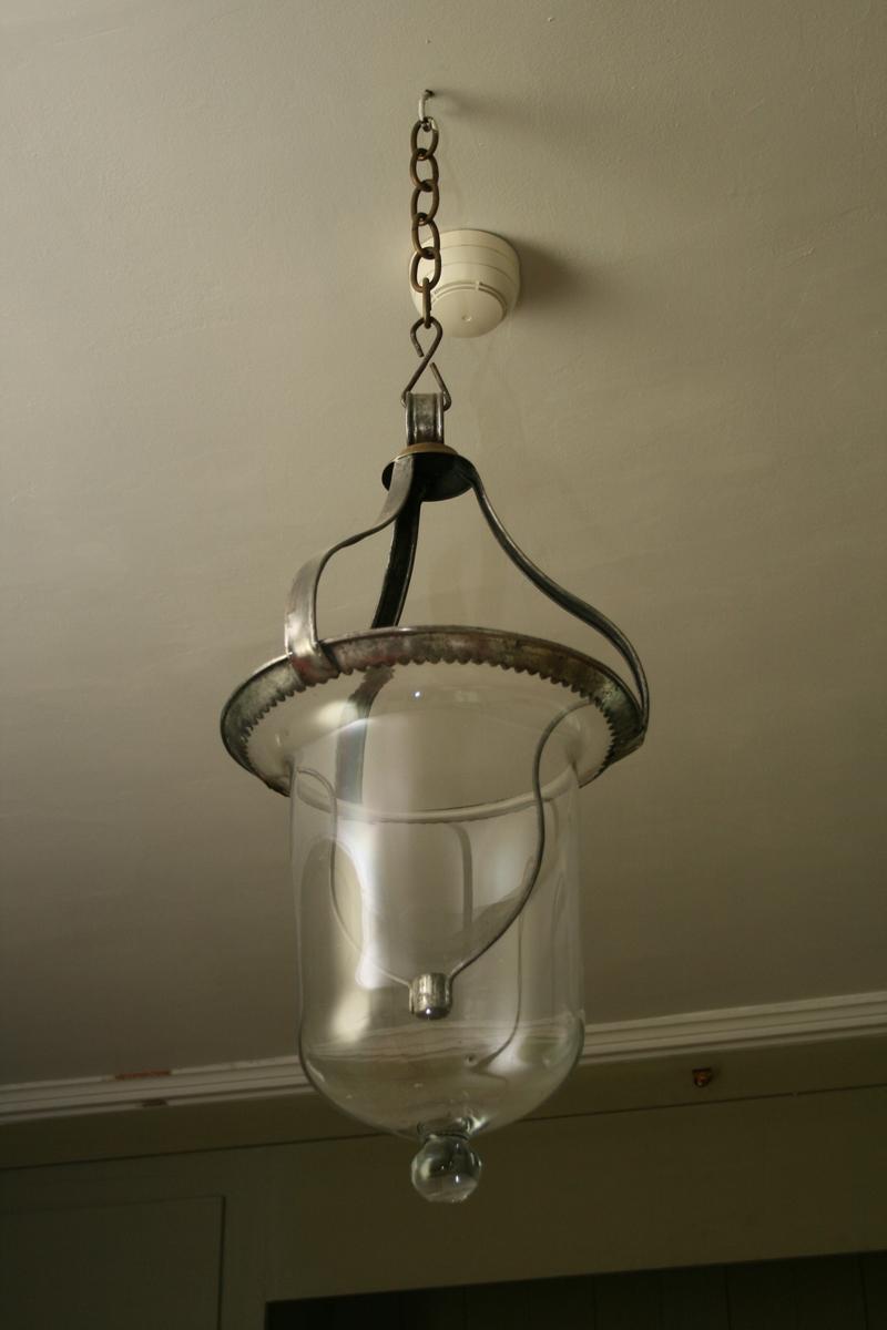 Glassampel for ett talglys. Metallbeslag som den henger i. Glassampelen ender i en kule.