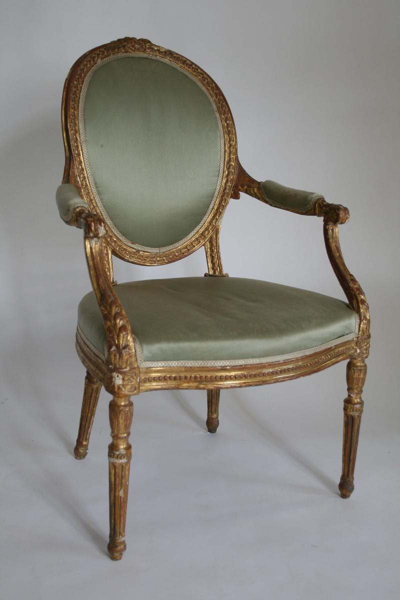 Forgylt armstol i Louis Seize-stil med oval rygg. Stoppet sete, rygg og armlener.