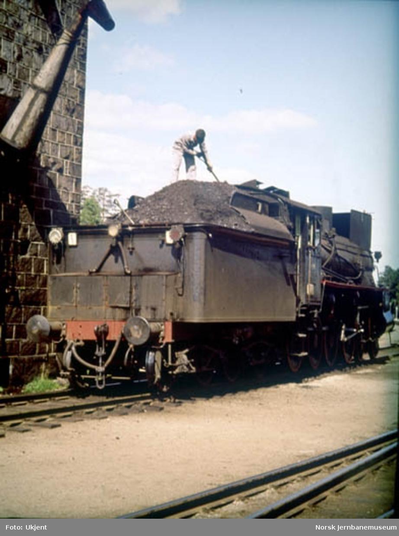 Damplokomotiv type 26c nr. 414(?) tar vann ved vanntårnet på Elverum stasjon