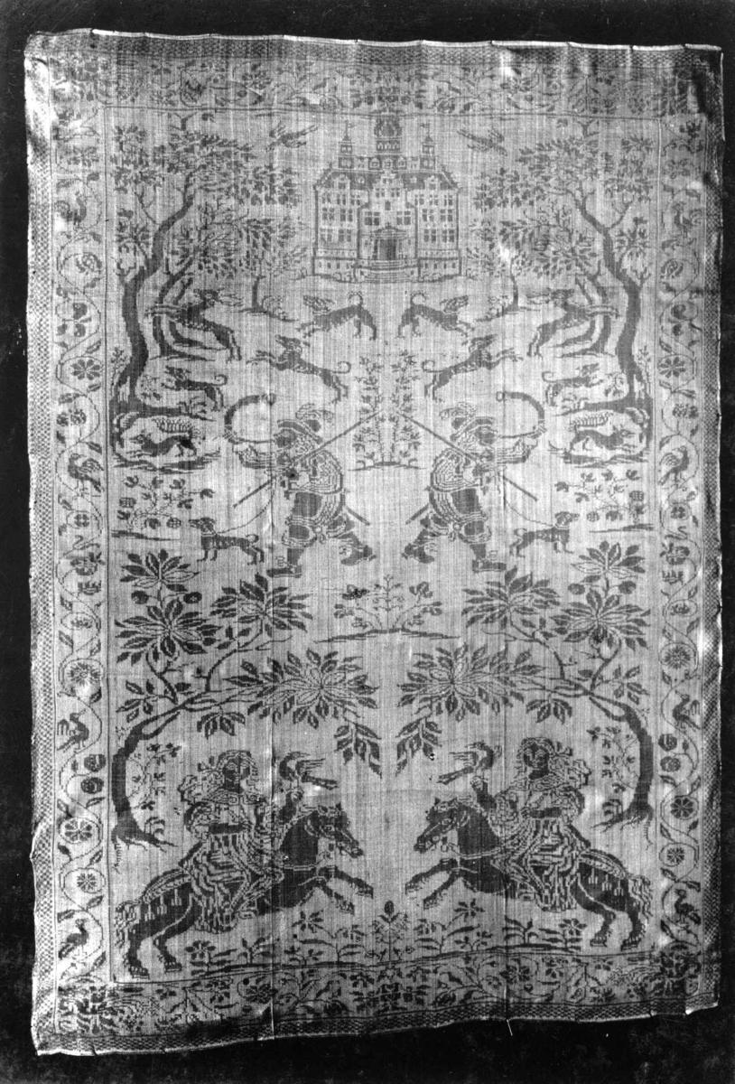 Hvit damaskserviett med motiv fra jaktscener, rankebord. Fra Holland, 1600-tallet.
