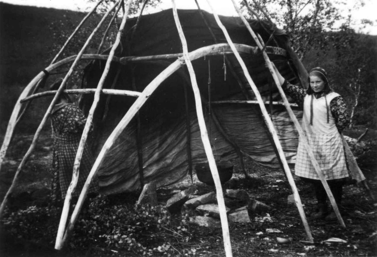 Demonstrasjon av oppsetting av telt, reisverket er satt opp og den en teltduken er lagt på. En kvinne står ved siden av. Sirma 1933.