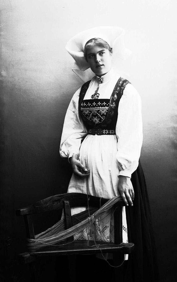 Studioportrett av kvinne i drakt og skaut, som står ved et hespetre. Bakgrunnen er nøytral.