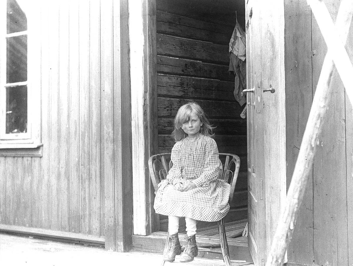 Holoa seter, Hadeland, Jevnaker, Oppland 1903. Gudrun Q. Wiborg sitter på stol i døråpning.